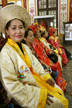 Women don Imperial silk garments and wait to have their photos taken seated on a royal throne