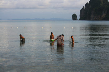 A family fishes at dawn in Loh Dalam Bay on phi phi island thailand