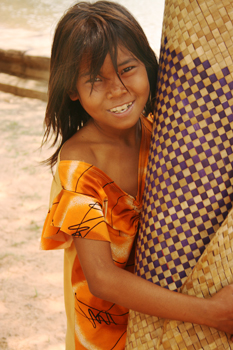 Child carries rattan carpets for sale in Cambodia