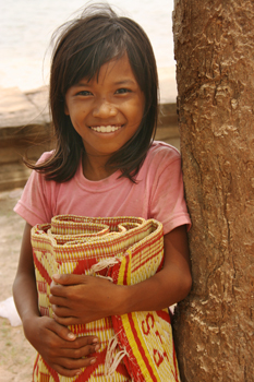 Cambodian child carries woven mats for sale