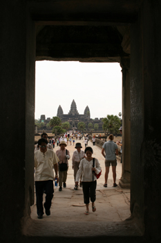 First view of Angkor Wat through an ancient stone doorway