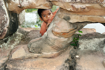 Cambodian boy shyly peeks out from behind the statues lining a bridge