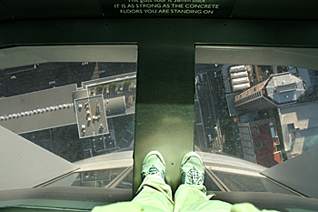 Standing over the glass floor n the Sky Tower in Auckland New Zeaand