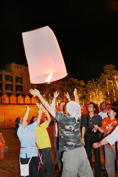 Launching a paper lantern with a center flame into the night sky for good luck