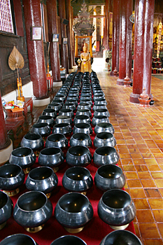 Worshipers place a coin in every bowl and say a prayer with each coin dropped at Wat Pan On in Chiang Mai Thailand