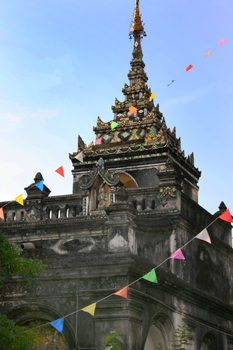 Multi-colored prayer flags adorn the ancient Chedi at Wat Pa Pao Chiang Mai Thailand