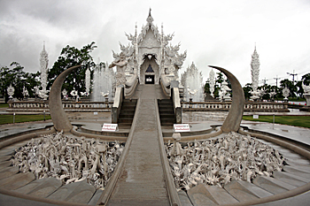 The pit on either side of the walkway leading to the main entrance at Wat Rong Kuhn in Chiang Rai is filled with a sculpture of bleached white bones