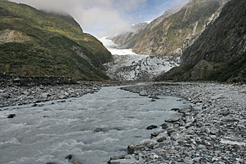 Glacier melt river water is grey from the rock powder it carries in Franz Josef New Zealand