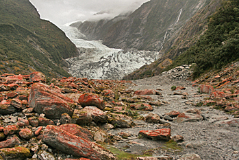 Red algae and green moss stained boulders litter the river bed in Franz Josef New Zealand