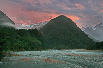 Sunset over mountains and river in Franz Josef New Zealand
