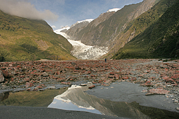 Mirror image of mountains and glacier in melt-water pond on the way to the foot of the Franz Josef glacier in New Zealand