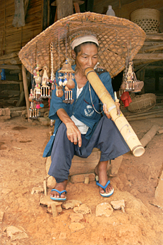 Akha (Kaw) traditional dress, posing for photos with opium pipe northern Thailand