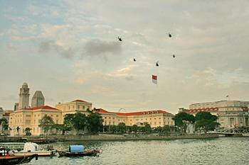 Helicopters fly in formation over Singapore, carrying the Singaporean flag