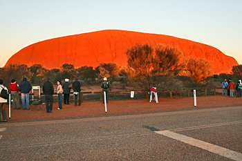 Ayers Rock (Uluru) glows orange at sunrise Australia