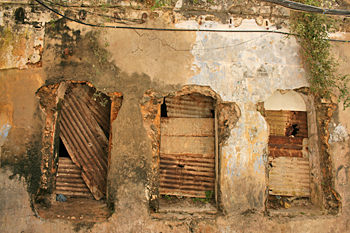 Funky boarded windows in crumbling adobe house in Stone Town Zanzibar