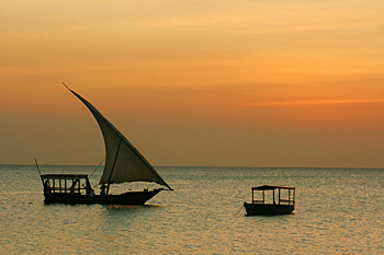 Traditional dhow sails through an orange sunset on Zanzibar