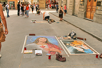 Street artists, painting ON the street in chalk for donations in Florence Italy