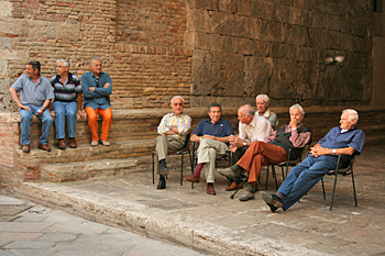Locals sit in the piazza and watch tourists in San Gimignano Italy