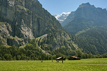 Crossing a high mountain meadow and river in the Bernese Oberland Switzerland