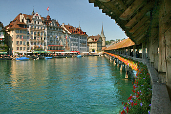 Crossing the Reuss River via old wooden Chapel Bridge in Lucerne Switzerland