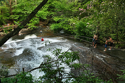 Kids climb up Sliding Rock and shimmy down on their rear ends, riding the whitewater to the bottom