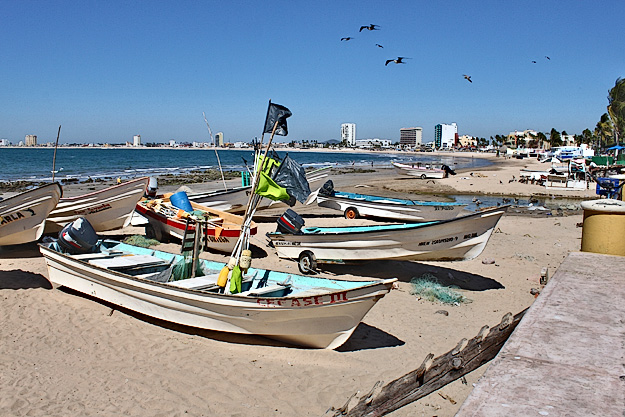 Fishermen pull their boats up onto the beach in Mazatlan Mexico