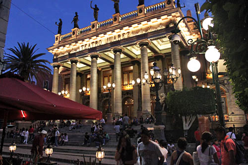 At night, crowds gather on the steps of the illuminated Teatro Juarez in Guanajuato Mexico