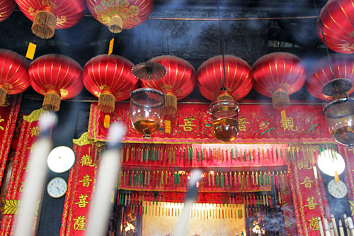 Smoke from my three large joss sticks floats toward Chinese lanterns that line the ceiling at Kwan Yin Buddhist temple in George Town