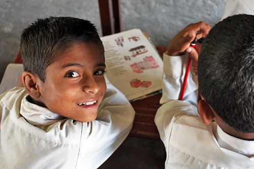 Kids study English manual at Annapurna School under the direction of Volunteer English teachers