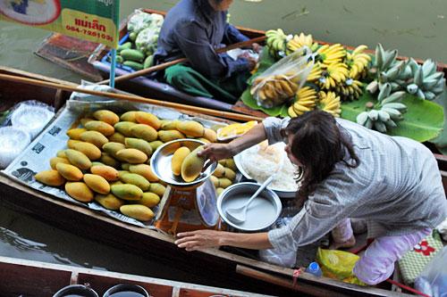 Buying sticky rice and mangoes from a boat vendor at the Damnoen Saduak Floating Market near Bangkok