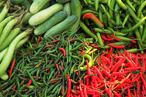 Piles of glistening vegetables, like these multi-colored hot peppers