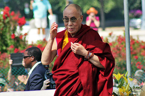 Dalai Lama on stage at the Capitol lawn; photographers and security in the background