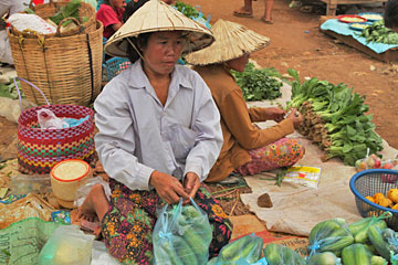 Women sell produce at market under blazng sun in Pakse, Laos
