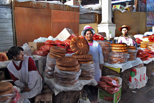 Quechua women at San Pedro Market in Cusco stand aside stacks of bread rounds
