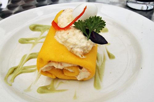 Peruvian Causa: Mashed yellow potato dumpling molded around crab on a bed of avocado sauce, topped with a Quail egg