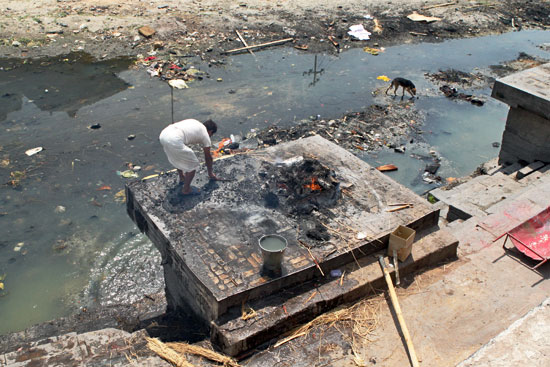 Priest sweeps away ashes after a cremation at the ghats of Pashupatinath Temple