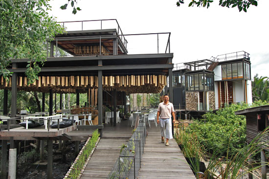 "Owner Joey Tulyanond shows off Bangkok Tree House restaurant with elevated glass ""nests"" in the background"