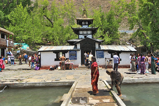 Fully clothed worshipers immerse in the freezing cold holy pools in front of Muktinath, one of the eight most sacred Hindu shrines in the world