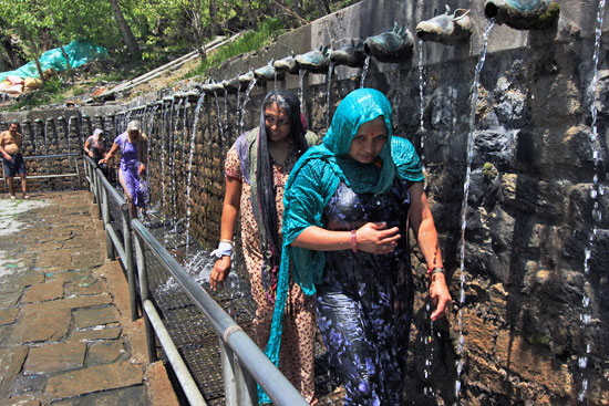 Devotees walk or run through the 108 holy fountains at Muktinath