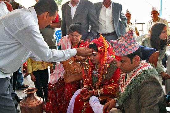 Guest applies tika to foreheads of bride and groom after wedding ceremony