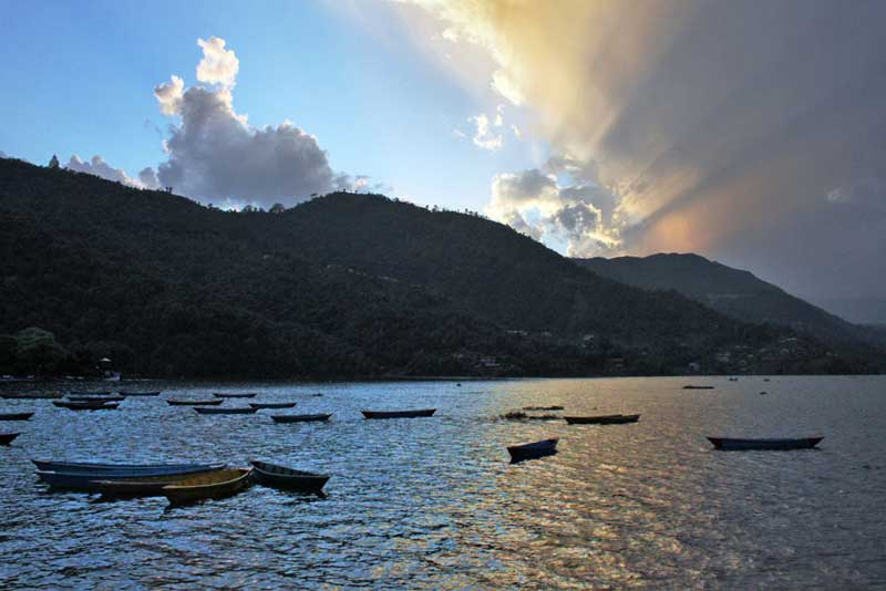 Sun sets behind the mountains at Phewa Lake in Pokhara, Nepal