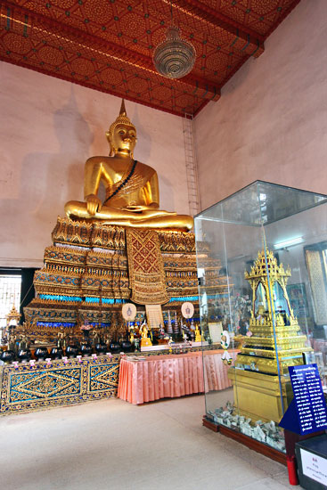 "Phra Phutthanak Buddha Statue, in the pose of ""Conquering Mara"" dominates the Vihara. The glass case in front holds relics of the Buddha discovered during the restoration of the Chedi."