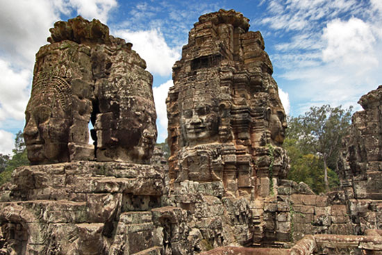 Buddha sculptures gaze enigmatically from the towers of Bayon temple