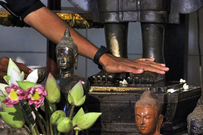 Washing the feet of the bronze statues of Preah Ang Chek and Ang Chom is believed to bring good luck