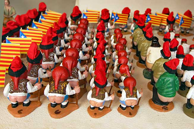 "Caganers, traditional figurines from Catalonia, Spain, wear the traditional hat called a barretina and are always displayed ""bare-bottom,"" squatting over a pile of ""poop."""