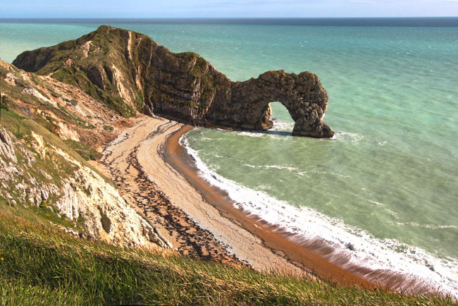 Durdle Door, carved by eons of waves and weather, separates Man O' War Cove from Durdle Cove on the South Coast hiking path in County Dorset, England