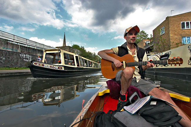Ride on a small wooden boat offers water-level views of narrowboats plying Regent's Canal in Camden Town