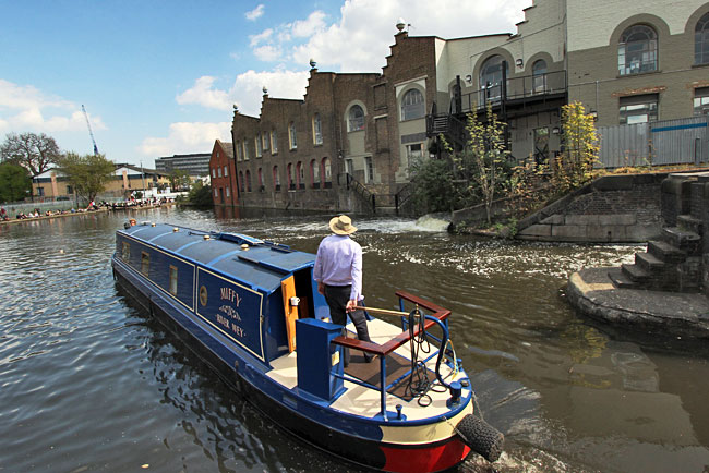 Narrowboat motors into lagoon after negotiating narrow locks at Camden Town London