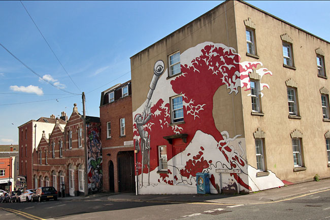 Giant wave surges over brick wall of a building in the Stokes Croft area of Bristol