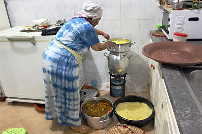 Family prepares cous cous in the traditional manner in a Marrakech home